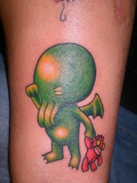 Leg band tattoo,creature monster child crying with toy