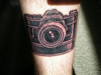 Leg tattoo, designed black and pink camera